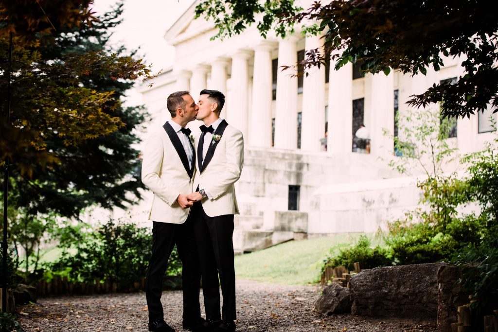 Gay couple in white tuxes holding hands and kissing