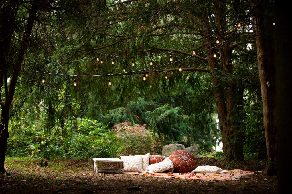 A table, and pillows sit on a blanket under greenery and lights