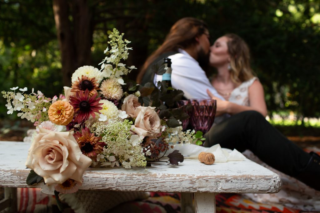 a floral bouquet with deep reds, tans, creams and oranges sits in front of a couple as they kiss