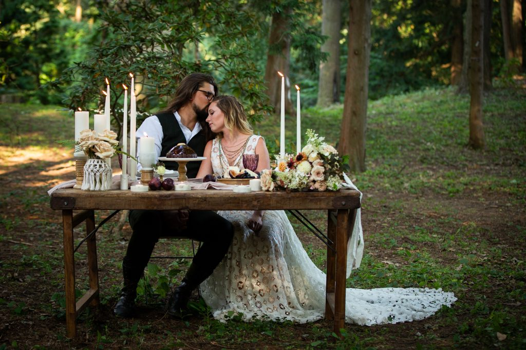 A man and a woman sit at a table for two in the woods, There are candles and florals on the table. He kisses her head as she leans into him.
