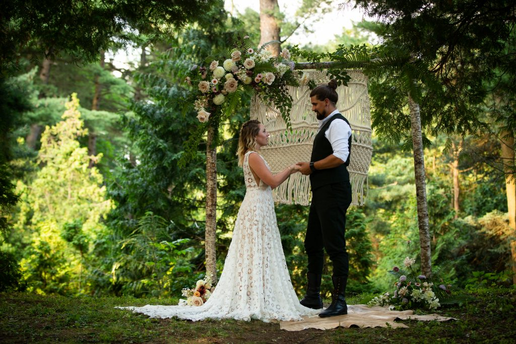 a man and a woman stand in front of a birch tree arch, face to face, holding hands. The woman wears a white full length dress, the man in dark pants and a vest with white shirt. The arch is covered with florals and there is a macrame piece hanging from it.