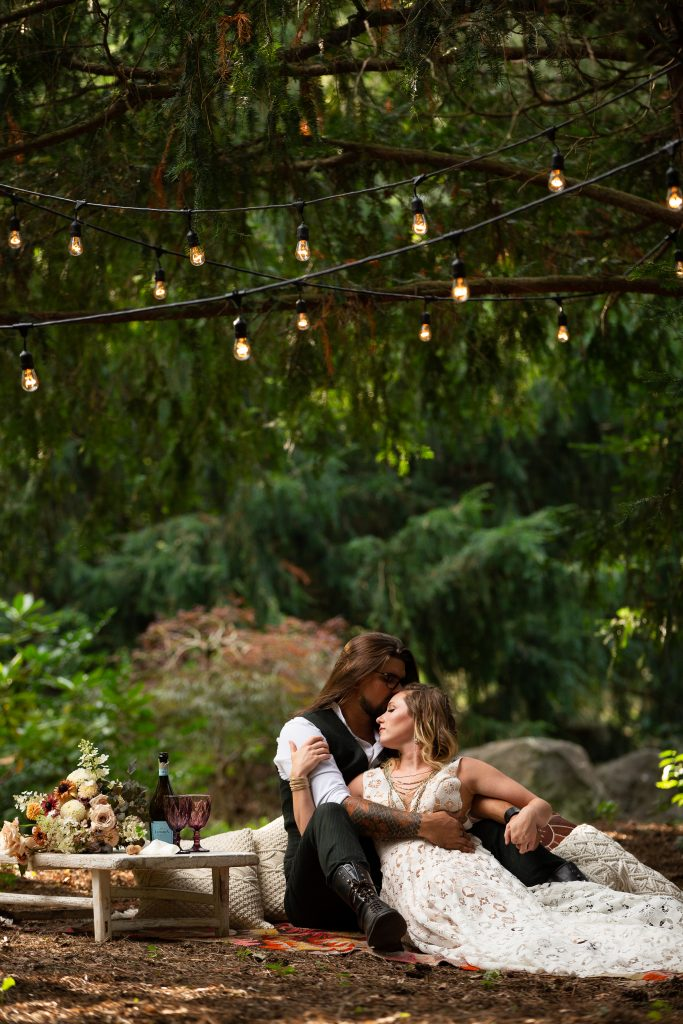 A man in black pants, white shirt and vest and a woman in a wedding dress sit on a blanket under lights, surrounded by lush greenery, embracing. There is a table with wine glasses and florals next to them.