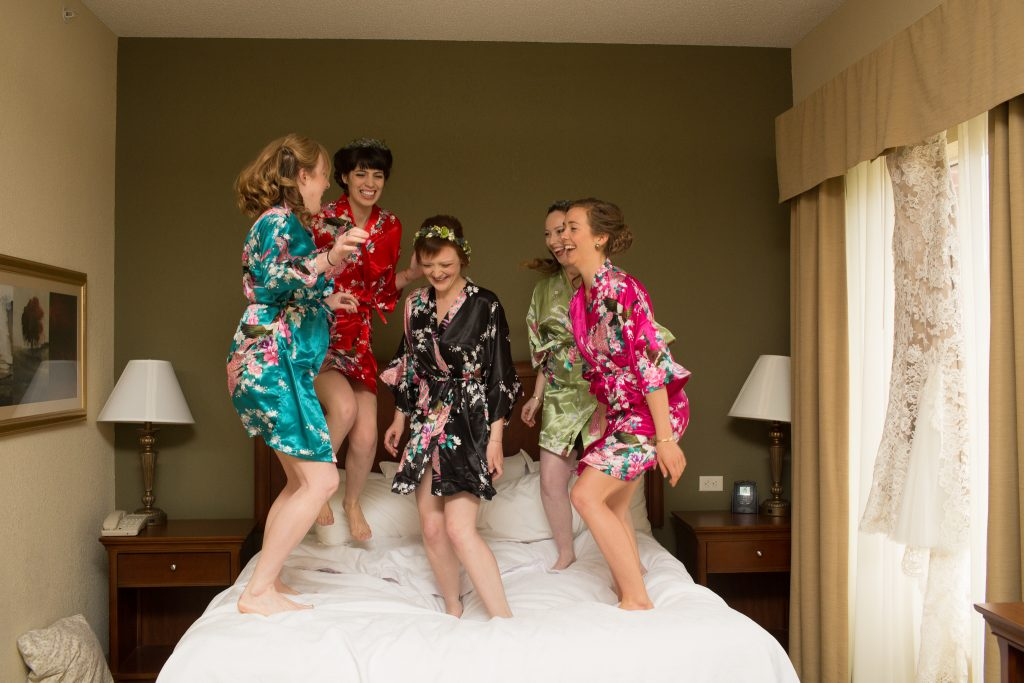 women in colorful robes jump on a bed surrounding a woman in a black floral robe with a crown on flowers on her head
