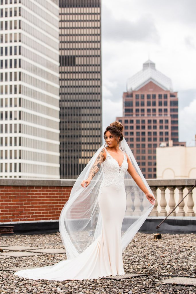 bride in fitted cream dress and long veil stands on rooftop with city view behind her